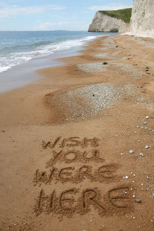 'Wish you were here' written in the sand on a peaceful beach - good copy area