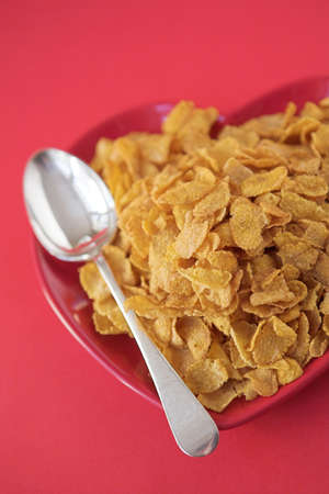Cornflakes & spoon on a heart shaped plate - healthy eating concept. Shallow dof