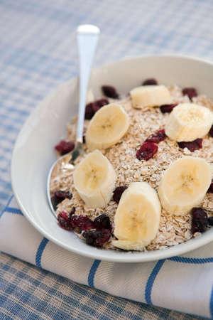 Porridge oats, cranberries & sliced banana ready for breakfast - Shallow dof