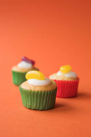Selection of fairy cakes with jelly beans on orange - shallow dof photo