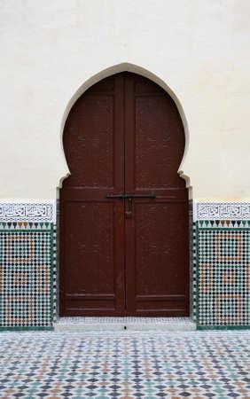 Moroccan doorway bordered by stucco & tilework photo