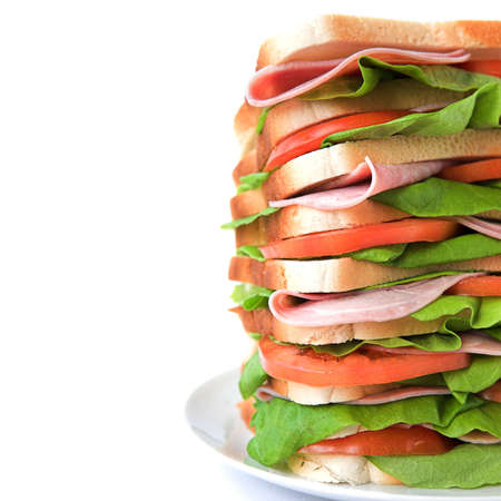 Tall sandwich of ham, tomato & lettuce on white bread - isolated on white photo