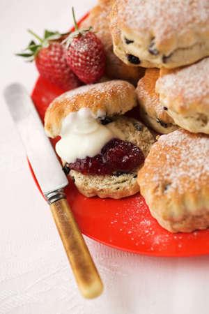 Scones & strawberry jam with cream - shallow dof Standard-Bild