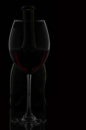 Wine glass & bottle on black - deliberate copy area to the right