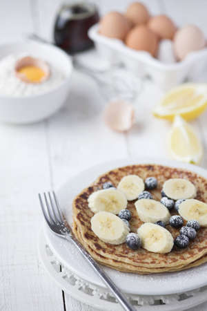 Freshly prepared crepes with banana & blueberries - shallow dof