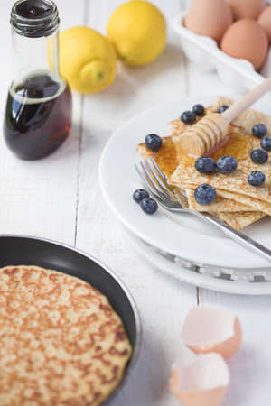 Freshly prepared crepes with maple syrup & blueberries - shallow dof