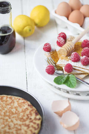 Freshly prepared crepes with raspberries - shallow dof