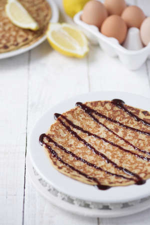 Freshly prepared crepes with chocolate sauce - shallow dof
