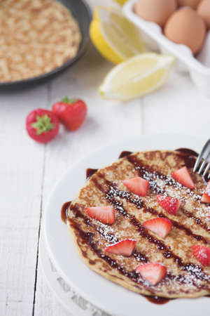 Freshly prepared crepes with strawberries - shallow dof