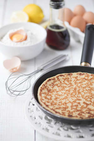Freshly prepared crepes with maple syrup - shallow dof