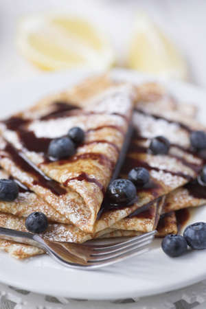 Freshly prepared crepes with blueberries & chocolate sauce - shallow dof