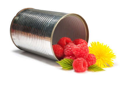 Delicious raspberries and a beautiful yellow flower in a silver tin can photo