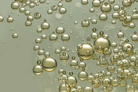 Many small air bubbles rising in golden champagne Фото со стока