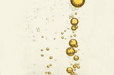 Yellow bubbles flowing over a white background Standard-Bild
