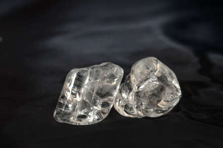 refelction: Two ice cubes laying on black silk fabric