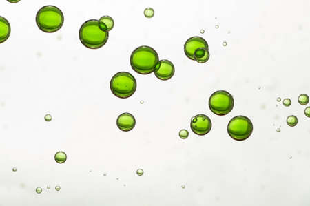 green ink: Green ink bubbles isolated over a light blurred background