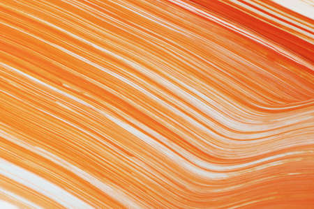 Orange and white paint mixed together in linear pattern.