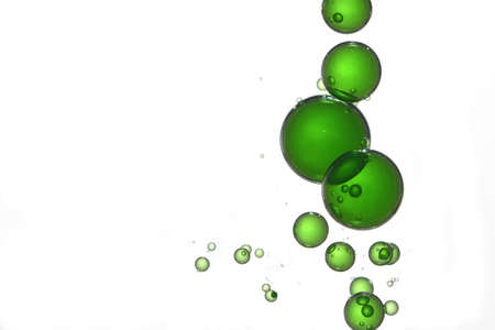 Green gradient liquid bubbles flows over a white surface.