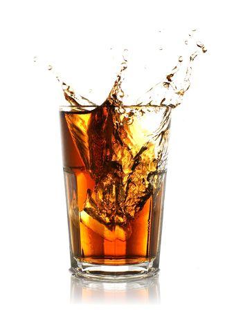 ice cube splashing into glass of coke Stock Photo