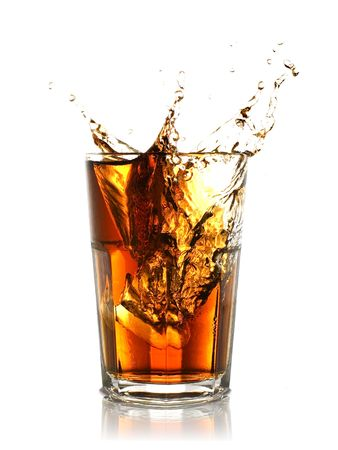 ice cube splashing into glass of coke Stock Photo