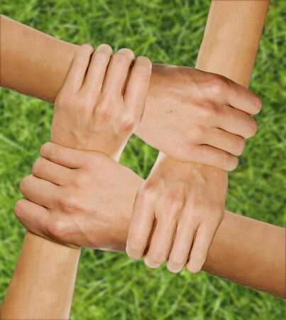 hands joined together over grass underground photo
