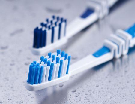 two tooth brushes on wet surface Zwei Zahnb�rsten auf nassem Untergrund