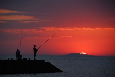 Sea sunrise and two men fishing Stock Photo - 2102666