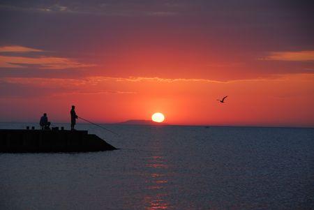Sea sunrise and two men fishing Stock Photo - 2102667