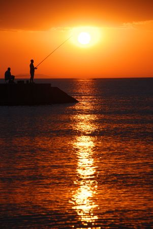 Sea sunrise and two men fishing Stock Photo - 2102673