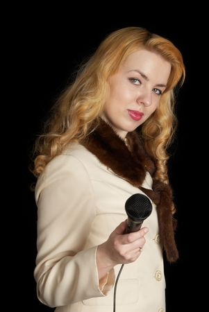 Pretty blond girl with microphone, black background photo