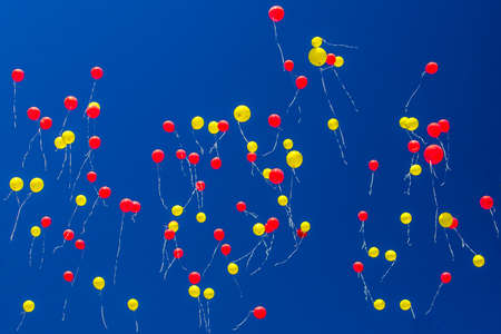 red and yellow balloons fly across the blue sky Stock fotó