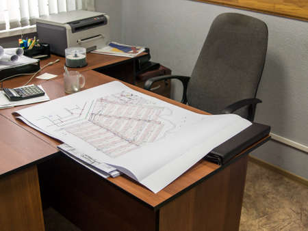 the workplace of the engineer foreman or construction manager, on the desktop is the project documentation for the new neighborhood, aside a glass mug with a spoon and a printer