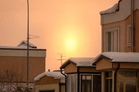 sunrise and winter morning in a cottage building, yellow sun and TV antenna, dark spots it is heavy snow, not grain or noise, selective focus