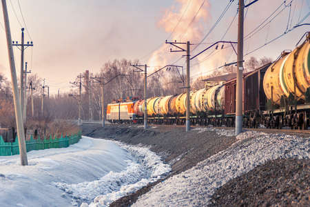 freight train out of the corner, industrial area behind trees Stok Fotoğraf