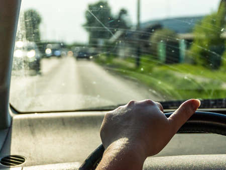 tired womans hand without a manicure is on steering wheel, car with dirty glass is driving in suburbs, selective focus