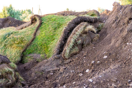 a pile of black soil with chunks of turf or pieces of old roll turf