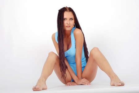 sitting beautiful girl in little blue dress. long legs photo