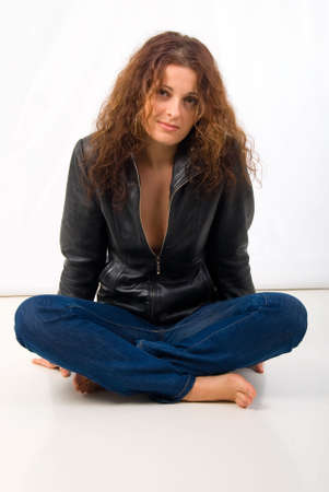 Sitting Young Woman In Leather Jacket. Studio Shoot Over White Background. photo