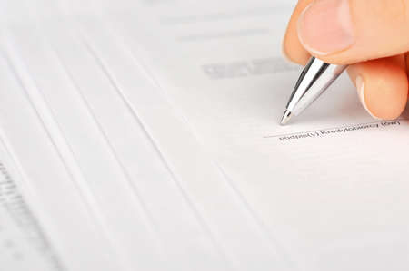 Female hand signing a bank account contract photo