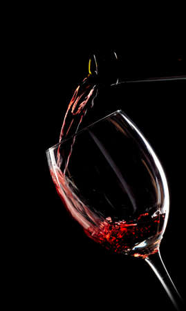 Red wine poured into a glass on black background Stock Photo
