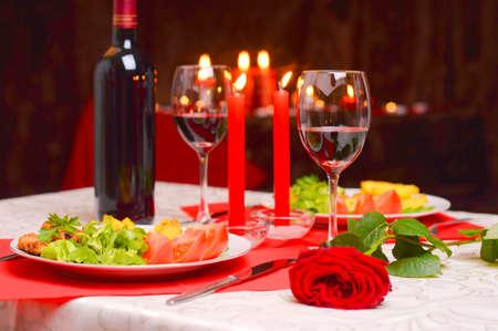 romantisch: Romantisches Abendessen mit Wein, Kerzen und einer roten Rose auf einem Tisch Lizenzfreie Bilder