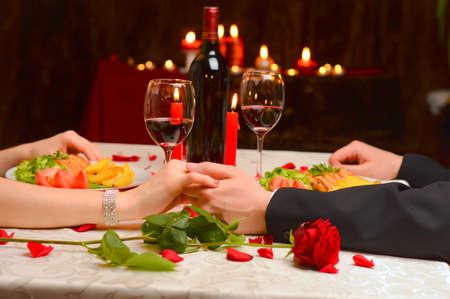 Een paar dat hun handen op een romantisch diner Stockfoto