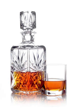 whisky bottle: Studio shot of whisky in a carafe and a glass isolated on white