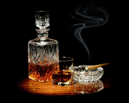 Studio shot of whisky in a carafe and glass and a cigar in ashtray isolated on black photo