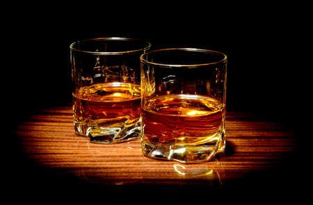 old bar: Two glasses of whiskey isolated on black
