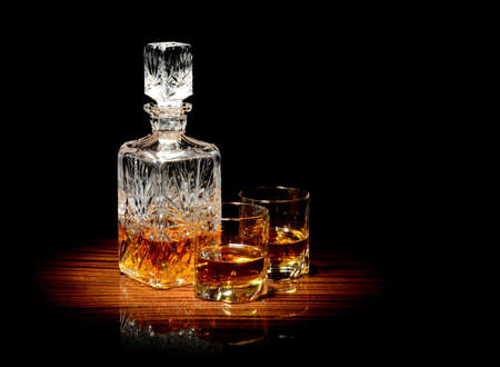 whiskey bottle: Studio shot of whiskey in a carafe and two glasses isolated on black Stock Photo