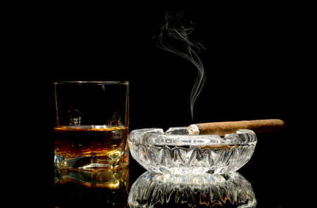 Studio shot of whisky in a glass and a cigar in ashtray isolated on black Stock Photo