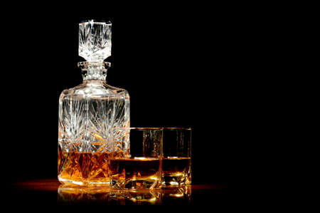 Studio shot of whiskey in a carafe and two glasses isolated on black Stock Photo