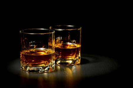 Two glasses of whiskey on black table