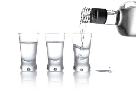 alcoholic drink: Close-up view of bottle and glasses of vodka poured into a glass isolated on white Stock Photo